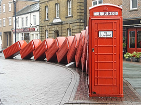 "Skulptur ""Out of Order"" von David Mach in Kingston upon Thames, eine Reihe rot lackierte Telefonzellen, die wie Dominosteine ineinander fallen. Foto: Kingston upon Thames"