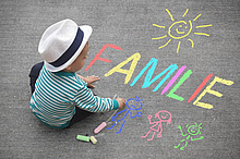 Child with chalk drawing the word familiy. Picture: motorradcbr/Fotolia.com